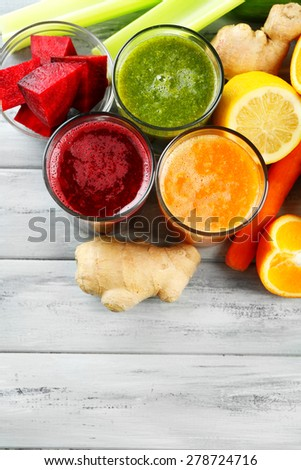 Assortment of healthy fresh juices on wooden table background - stock photo