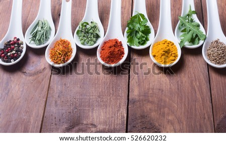 assortment of indian spices and herbs in ceramic spoon on wooden background