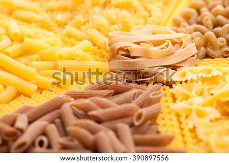 Assortment of italian pasta, five different varieties separated with curly spaghetti and bunch of noodles in the middle. Raw pasta texture background.