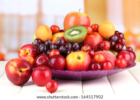 Assortment of juicy fruits on wooden table, on bright background - stock photo