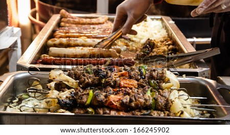 Assortment of  kebabs and grilled sausages and the hands of the seller which prepares the hot dog sandwich at Christmas market in Paris. Selective focus on the upper kebabs. - stock photo