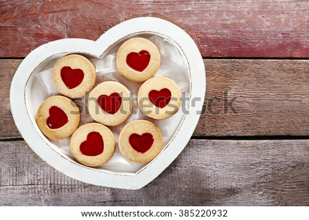 Assortment of love cookies in box on wooden background, closeup - stock photo