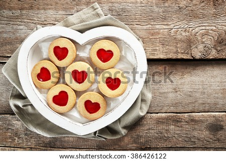Assortment of love cookies in box with cloth on wooden background, closeup - stock photo