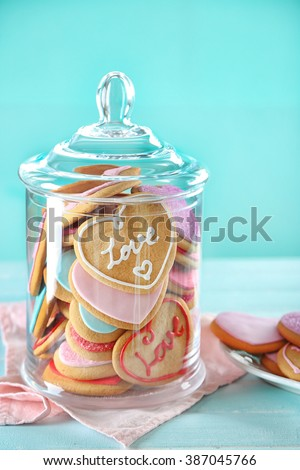 Assortment of love cookies in jar on blue background - stock photo