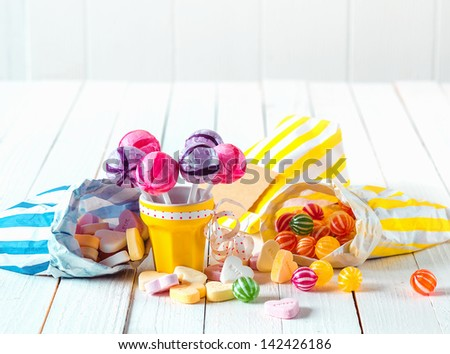 Assortment of many candy types with marshmallows and lollipops in bags and cup laid over a white wooden table - stock photo