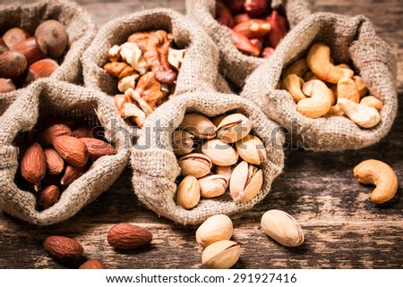 Assortment of nuts on wooden old table,healthy vegan food. - stock photo