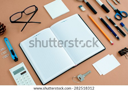 Assortment of Office Supplies Neatly Organized Around Note Book Open to Blank Page on Desk Top Surface - stock photo