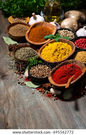 assortment of oriental spices on a wooden table, vertical, closeup