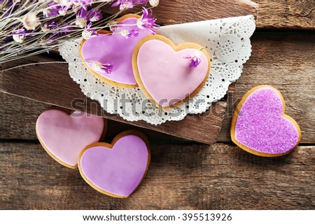 Assortment of pink love cookies on wooden background - stock photo