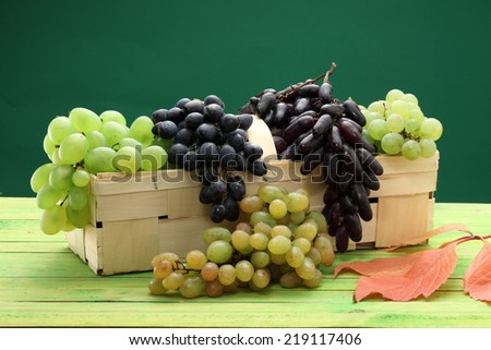 Assortment of ripe sweet grapes in a basket - stock photo