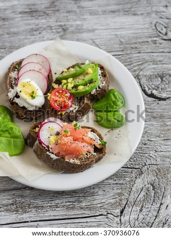 Assortment of sandwiches - sandwiches with cheese, radish, cucumber, quail egg, avocado and smoked salmon. Tasty breakfast, snack or appetizer with wine - stock photo