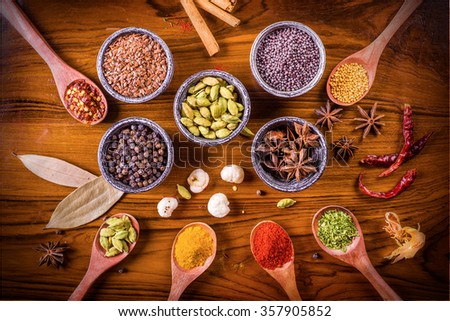 Assortment of spices and herbs in wooden spoons and stone spice bowls over polished textured wooden board. - stock photo