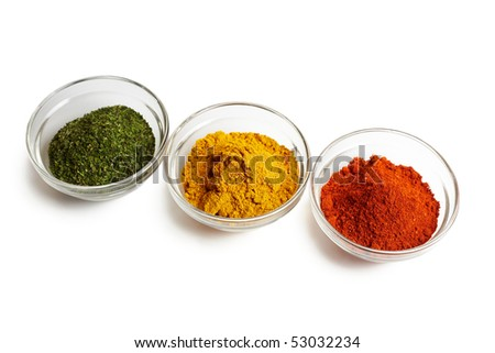 Assortment of spices in traffic light colours in glass bowls - stock photo