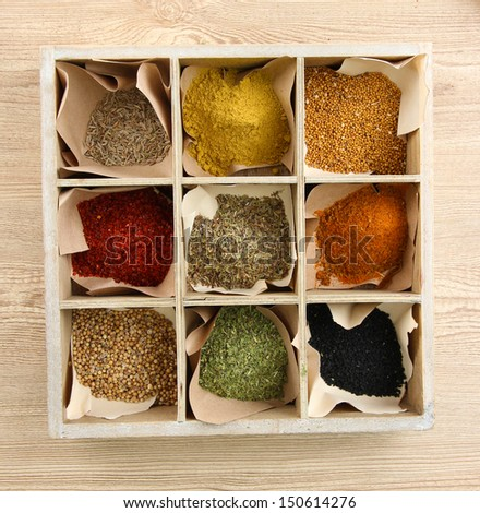 Assortment of spices in wooden box, on wooden background