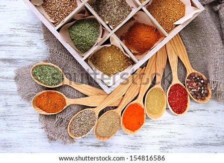 Assortment of spices in wooden spoons and box, on wooden background - stock photo