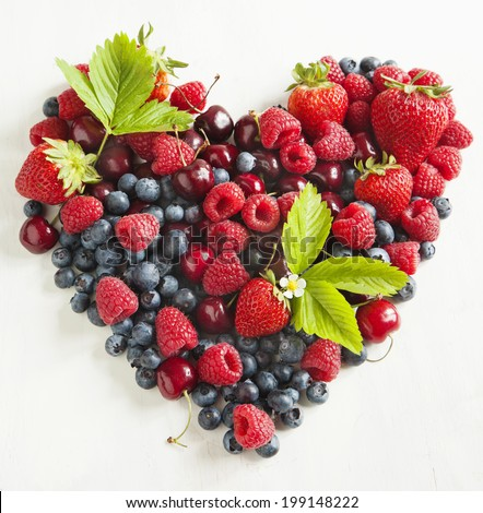 Assortment of summer fresh berries in the shape of heart  - stock photo