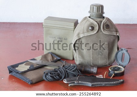 Assortment of survival hiking gear including first aid kit, canteen, knife, parachute cord, compass and map holder on old wood table - stock photo