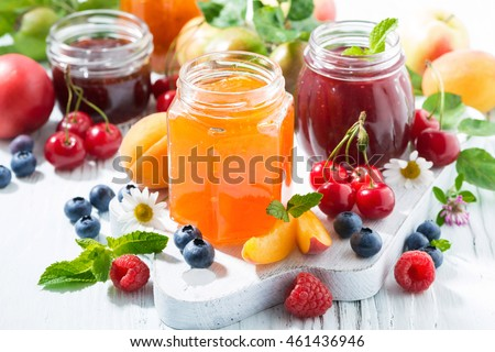 assortment of sweet jams and seasonal fruits on white table, closeup, horizontal