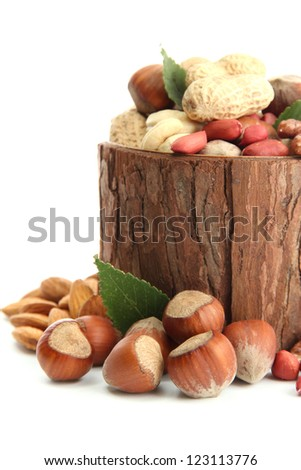 assortment of tasty nuts with leaves in wooden vase, isolated on white - stock photo