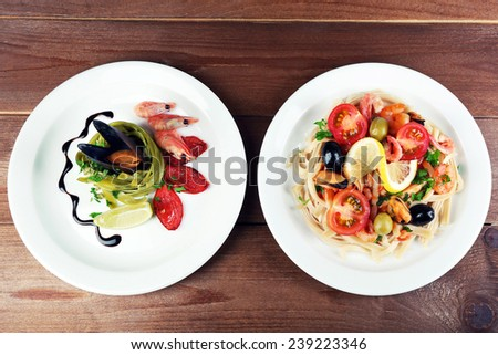 Assortment of Tasty pasta with shrimps, mussels, black olives and tomato sauce on plates on wooden background - stock photo