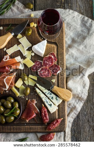 Assortment of various types of cheese and meat on wooden board, top view - stock photo