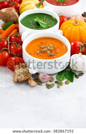 assortment of vegetable cream soups and ingredients on white background, vertical, closeup