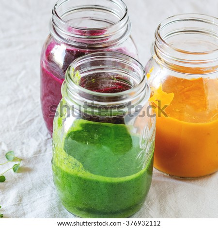 Assortment of vegetable smoothies from carrot, beetroot and spinach in glass jars. Over white tablecloth. Rustic style, natural day light. Square image with selective focus