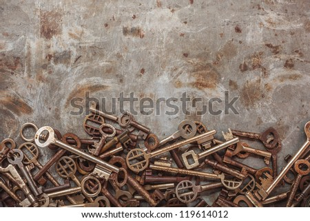 Assortment of vintage keys on a grungy steel background - stock photo