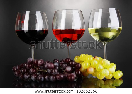 Assortment of wine in glasses on grey background - stock photo