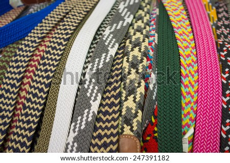 Assortment of woven textile belts on a street market stall