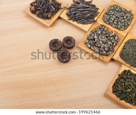 assortment set of dry tea in spoons, on wooden texture table background with copy space - stock photo
