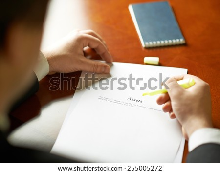 Asstets definition as a shallow depth of field close-up composition of a man in a business suit working with the text
