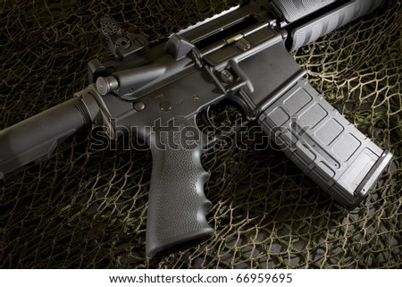 Assuaulte rifle that is on black and white netting - stock photo