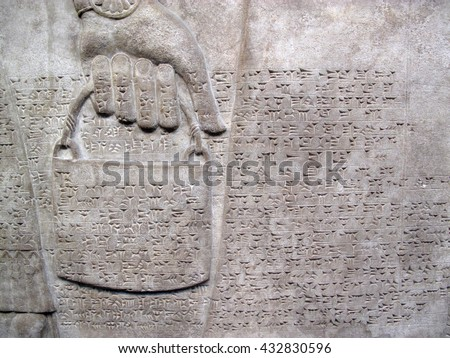 Assyrian relief 865-860 BC, showing cuniform script, of a royal helper carrying a bucket - stock photo