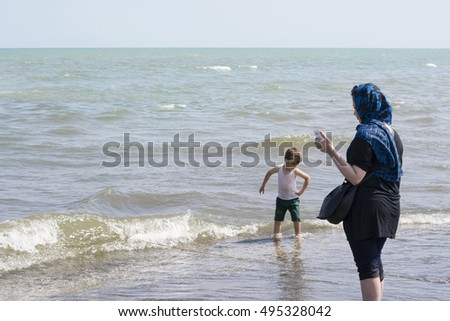 Astara- IRAN-September 22, 2016 Muslim Woman with Black Gown and His Son At Beach, Caspian Sea Shore. Gilan Province