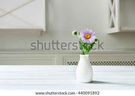Aster amellus flowers bouquet in white ceramic vase at wooden table. White shabby chic interior. Flower detail in interior design. Purple aster in vase. Violet Aster bouquet at home - stock photo