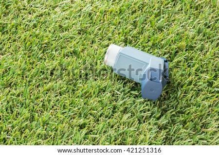Asthma inhaler and bottle of medicine on artificial grass