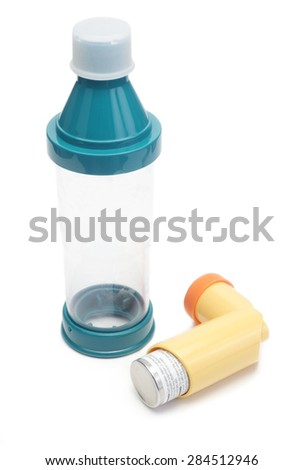 Asthma inhaler with inhalant spacer chamber on white. Albuterol sulfate is a non-trademarked, common medication name. - stock photo