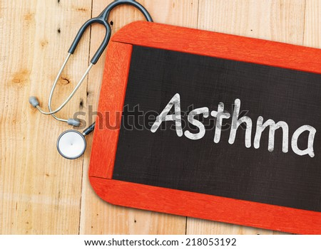 Asthma written on chalkboard and stethoscope.  - stock photo