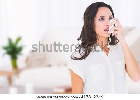 Asthmatic brunette using her inhaler against light bulb flower on dark wall - stock photo