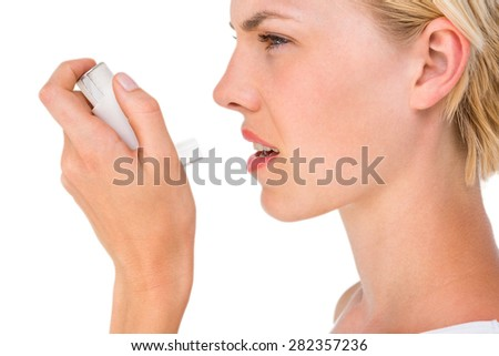 Asthmatic pretty blonde woman using inhaler on white background - stock photo