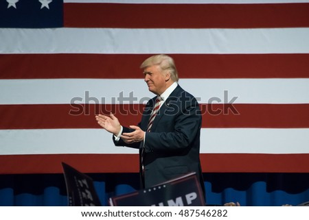 ASTON, PA - SEPTEMBER 22, 2016: Donald Trump enters the stage and walks by the American Flag. Trump is the Republican nominee for US President and he held a rally at Sun Center Studios.