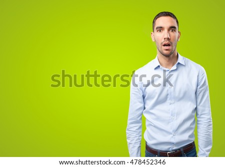 Astonished businessman on green background