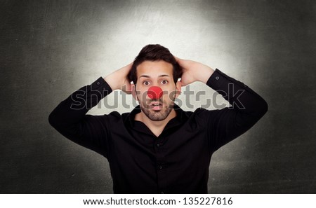 Astonished businessman with clown nose on a over gray and irregular background - stock photo
