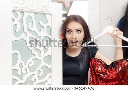 Astonished Girl Trying on Red Party Dress in Dressing Room - Funny fashion with a clothes hanger deciding what to wear  - stock photo