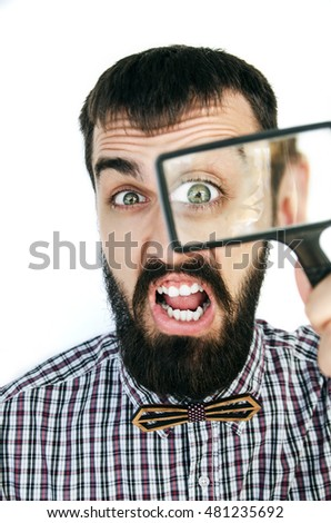 Astonished handsome bearded man looking through magnifying glass on white background