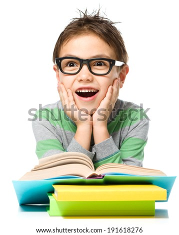 Astonished little boy is reading a book while wearing glasses, isolated over white - stock photo