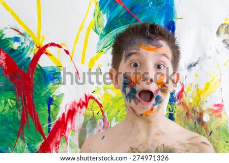 Astonished little boy with his face covered in colorful paint splodges gawping at the camera in front of a modern abstract painting in vibrant colors - stock photo