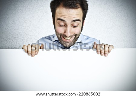 Astonished man holding an empty white board  - stock photo