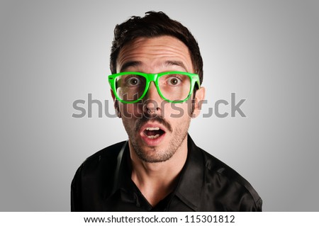astonished man with green eyeglasses on gray background